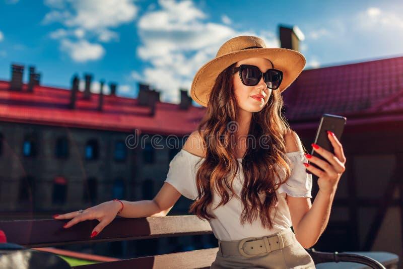 Jonge modieuze vrouw die hoed en zonnebril dragen en smartphone in openlucht gebruiken Het modieuze reizigersmeisje ontspannen stock afbeeldingen