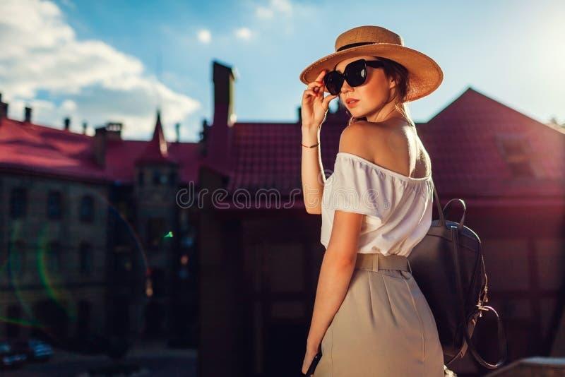 Jonge modieuze vrouw die hoed en zonnebril in openlucht dragen Modieus meisje met rugzak en telefoon die in Lviv lopen royalty-vrije stock foto
