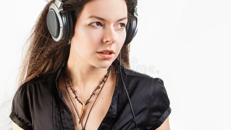 Jonge modieuze vrouw in grote hoofdtelefoons die aan muziek luisteren en pret hebben royalty-vrije stock foto's
