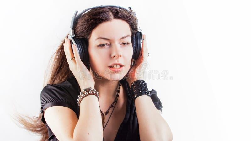 Jonge modieuze vrouw in grote hoofdtelefoons die aan muziek luisteren en pret hebben royalty-vrije stock afbeelding