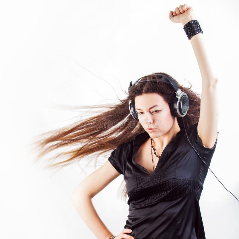 Jonge modieuze vrouw in grote hoofdtelefoons die aan muziek luisteren en pret hebben stock afbeeldingen