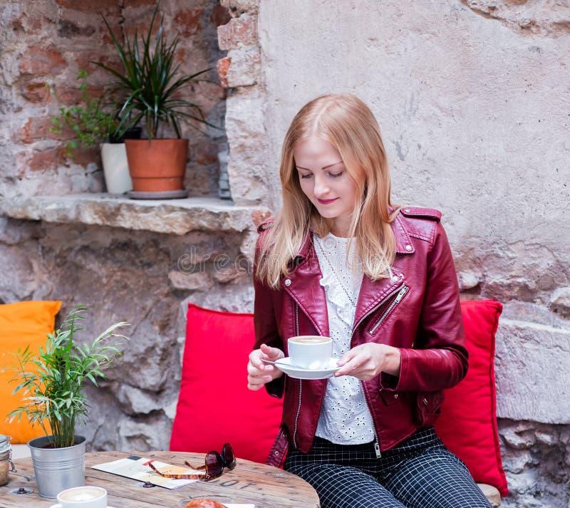 Jonge modieuze vrouw met koffie en croissantzittingsoudoors bij het koffieterras royalty-vrije stock foto