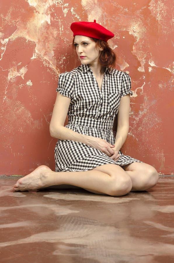 Jonge modieuze vrouw in modieuze kleding in uitstekende stijl en een rode baret royalty-vrije stock foto's