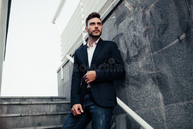 Jonge modieuze zakenmanmens met een baard in een modieus kostuum en jeans Modern beeld van de bedrijfsjeugd Het bevindt zich op royalty-vrije stock afbeeldingen