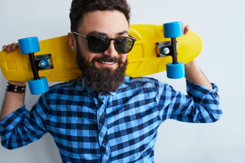 Jonge modieuze zekere gelukkige knappe mens met skateboard stock afbeeldingen