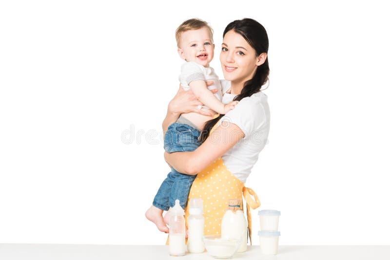 jonge moeder in de babyjongen van de schortholding bij lijst met kinderenvoedsel stock fotografie