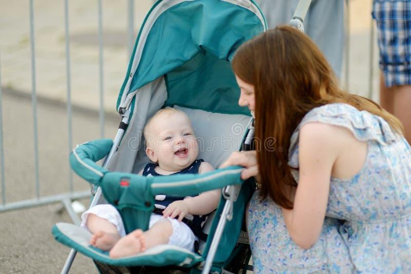 Jonge moeder die aan haar baby in een wandelwagen spreken royalty-vrije stock foto