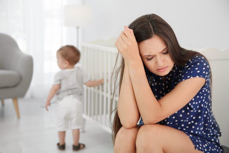 Jonge moeder die aan postnatale depressie aan weinig baby in ruimte lijden royalty-vrije stock foto's