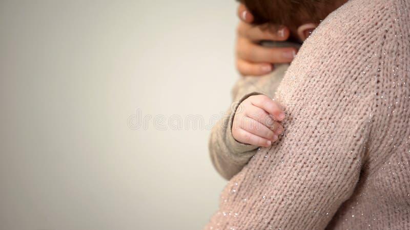 Jonge moeder die aanbiddelijke zuigeling in wapens knuffelen, uiterst kleine handclose-up, babyzorg stock fotografie