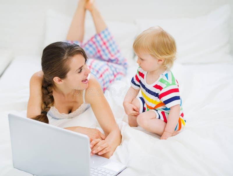 Jonge moeder die baby iets in laptop toont royalty-vrije stock foto