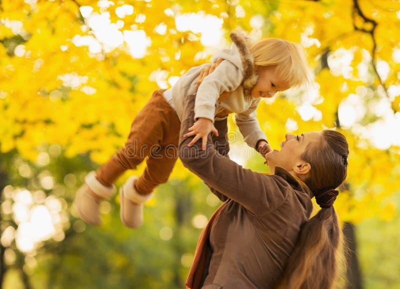 Jonge moeder die baby omhoog werpt stock afbeeldingen