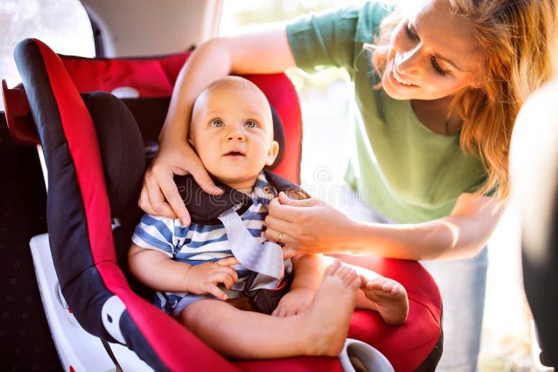 Jonge moeder die babyjongen in de autozetel zetten stock foto's