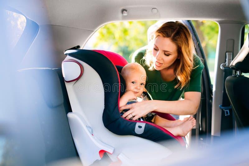 Jonge moeder die babyjongen in de autozetel zetten royalty-vrije stock afbeelding