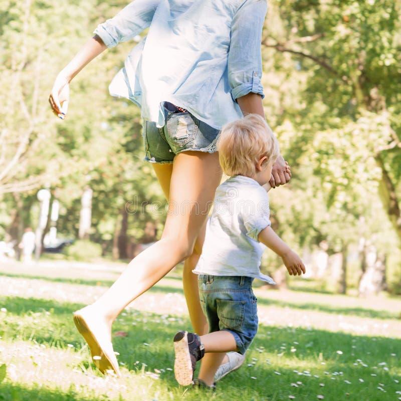 Jonge moeder die een gang met haar peuterzoon hebben in het park royalty-vrije stock foto's