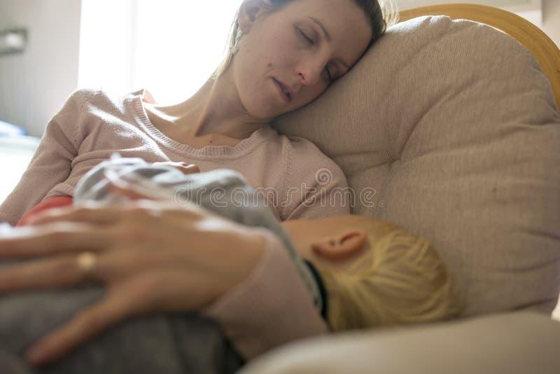 Jonge moeder die in een schommelstoel met babyslaap dutten in h royalty-vrije stock foto's