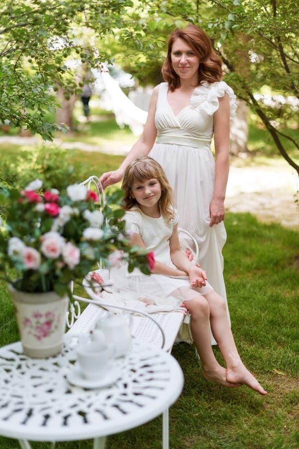 Jonge moeder die en pret met haar spelen hebben weinig dochter in groen de zomerpark Familiegeluk, kinderjarenconcept royalty-vrije stock fotografie
