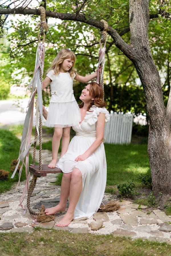 Jonge moeder die en pret met haar spelen hebben weinig dochter in groen de zomerpark Familiegeluk, kinderjarenconcept stock foto