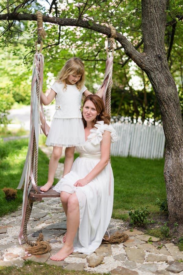 Jonge moeder die en pret met haar spelen hebben weinig dochter in groen de zomerpark Familiegeluk, kinderjarenconcept royalty-vrije stock foto