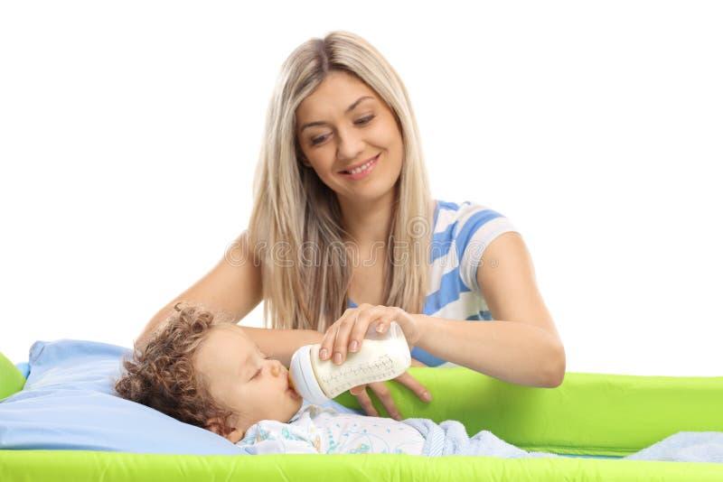 Jonge moeder die haar babyjongen met een fles melk voeden stock foto's