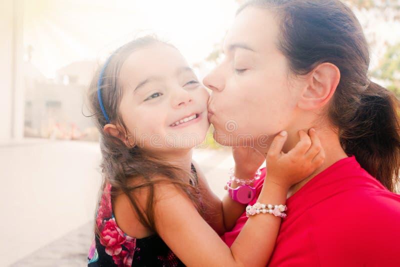 Jonge moeder die haar dochter kussen stock fotografie