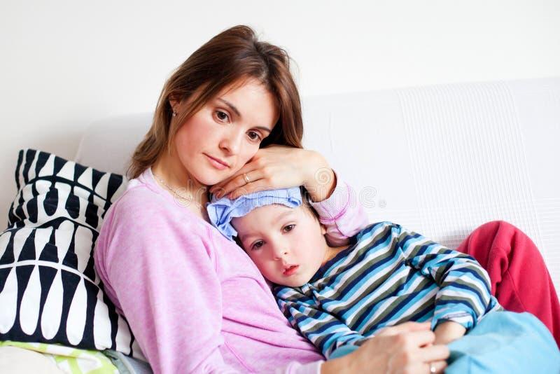 Jonge moeder, die haar houden kleine zieke jongen, natte doek op zijn voorst gedeelte stock foto's