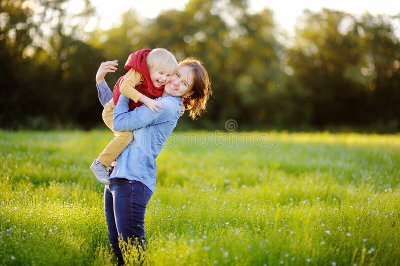 Jonge moeder die haar houden weinig zoon tijdens gang op het bloemengebied royalty-vrije stock fotografie