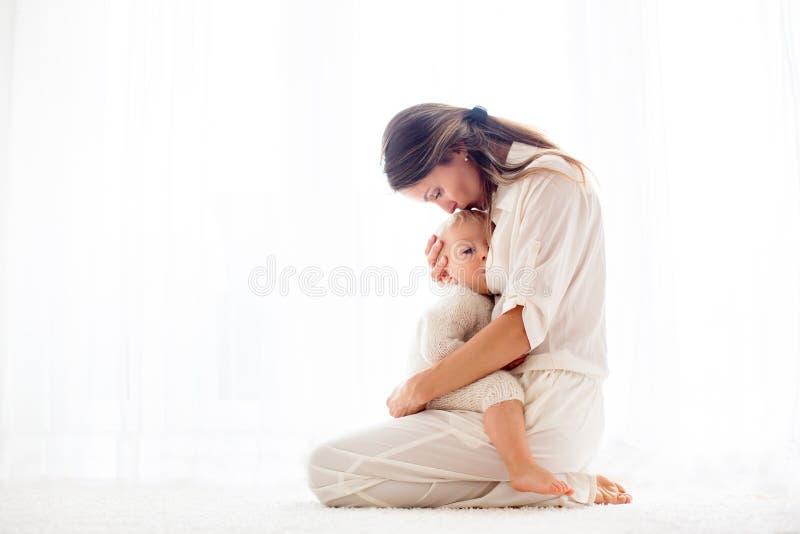 Jonge moeder die haar jongen van de peuterbaby de borst geven royalty-vrije stock afbeeldingen