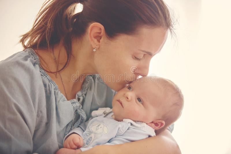 Jonge moeder, die haar pasgeboren babyjongen thuis kussen stock afbeelding