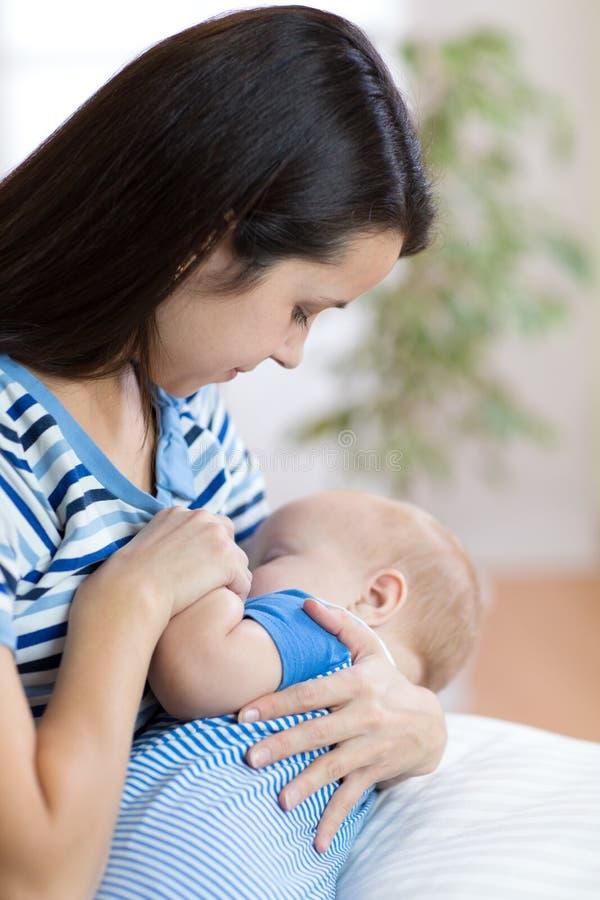 Jonge moeder die haar pasgeboren kind houden Mamma pleegbaby royalty-vrije stock foto's