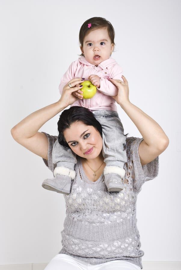 Jonge moeder die haar peuter op schouders houdt royalty-vrije stock afbeeldingen
