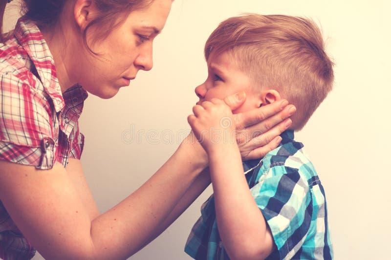 Jonge moeder die haar troosten weinig schreeuwend kind royalty-vrije stock foto's