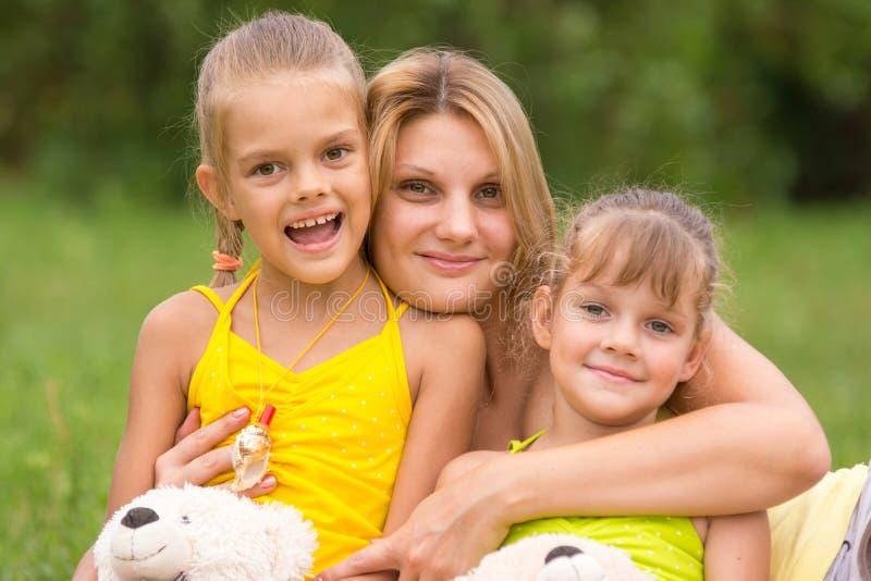 Jonge moeder die haar twee dochters koesteren stock afbeeldingen