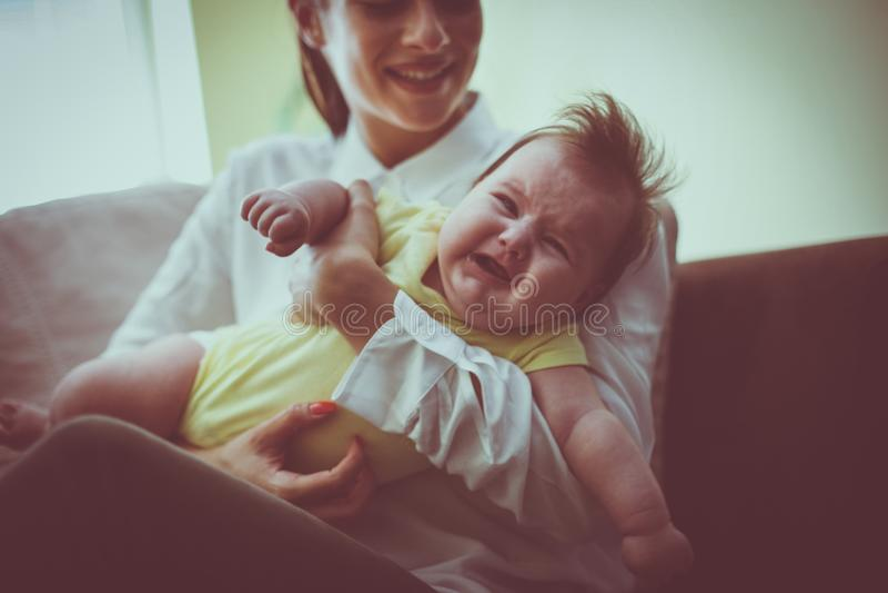 Jonge moeder die haar weinig babymeisje voeden stock fotografie