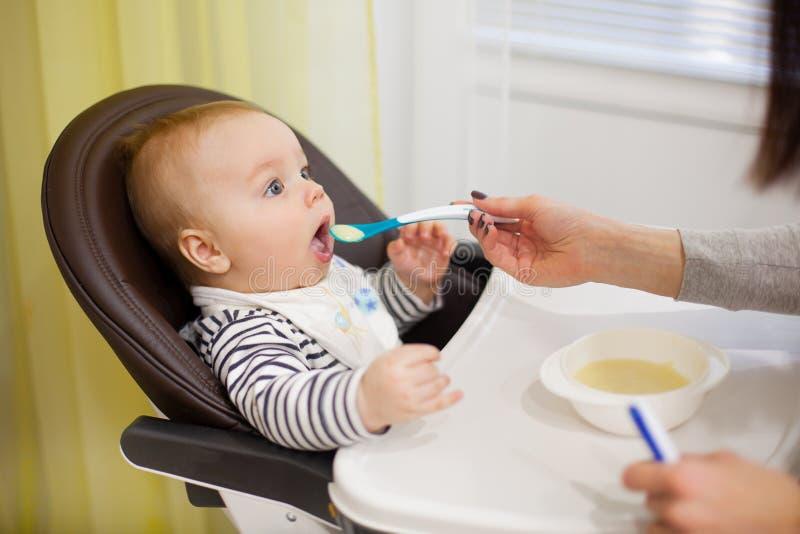 Jonge moeder die haar weinig babyzoon met havermoutpap voeden, die zitting als hoge babyvoorzitter voor het voeden stock foto
