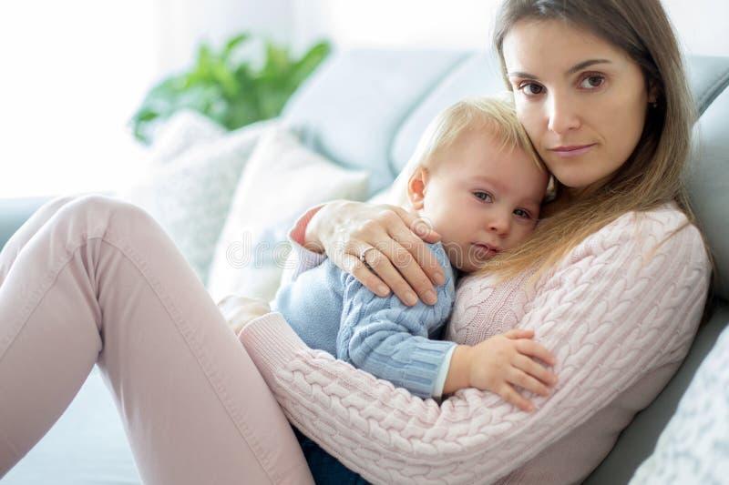 Jonge moeder, die haar zieke peuterjongen houden, die hem thuis koesteren stock afbeelding