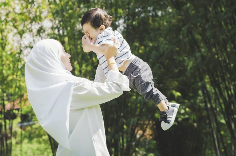 Jonge moeder die haar zoon koesteren bij park onder heldere zonnige dag voor royalty-vrije stock afbeeldingen