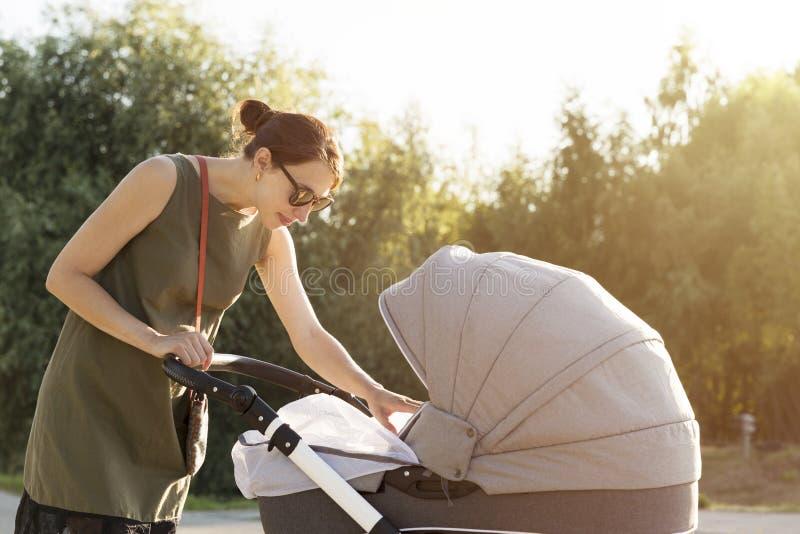 Jonge moeder die kinderwagen in park onderzoeken Moederstrollin royalty-vrije stock fotografie