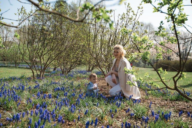 Jonge moeder die met een zoon van de babyjongen op een muscarigebied lopen in de lente - zonnige dag - druivenhyacint royalty-vrije stock fotografie
