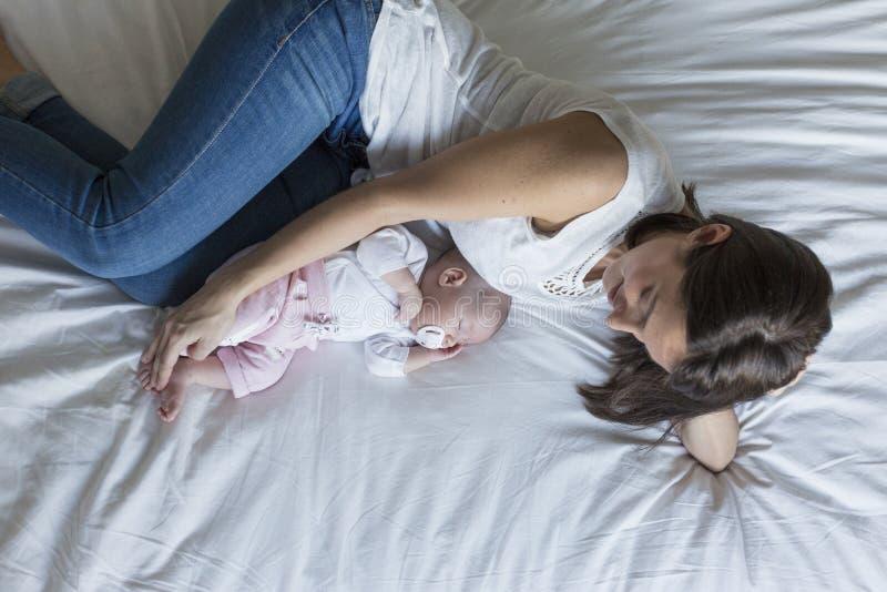 jonge moeder die op bed thuis met haar babymeisje liggen Familie en liefdeconcept stock foto's