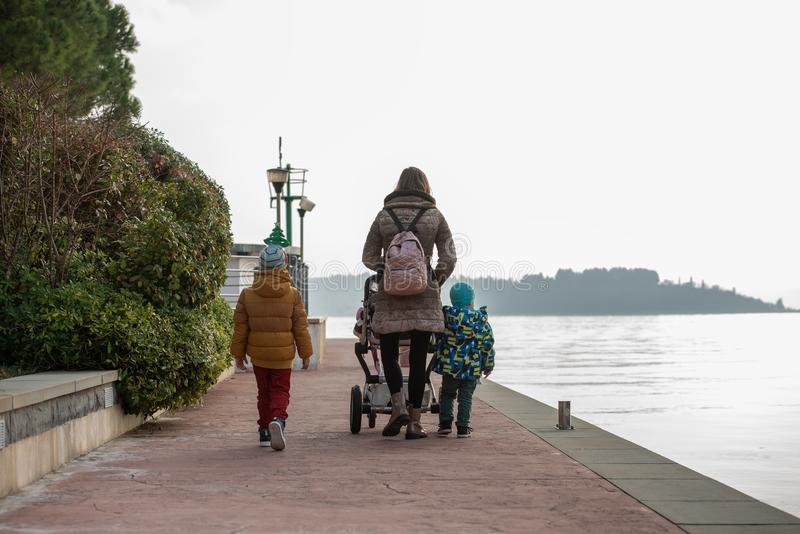 Jonge moeder die op een promenade langs het overzees lopen die een wandelwagen duwen stock foto's