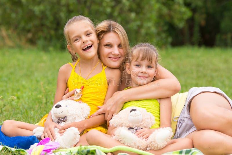Jonge moeder die op picknick twee dochters, vijf zeven jaar koesteren royalty-vrije stock afbeelding
