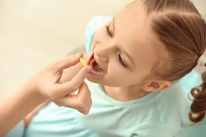 Jonge moeder die pil geven aan haar dochter, binnen stock fotografie