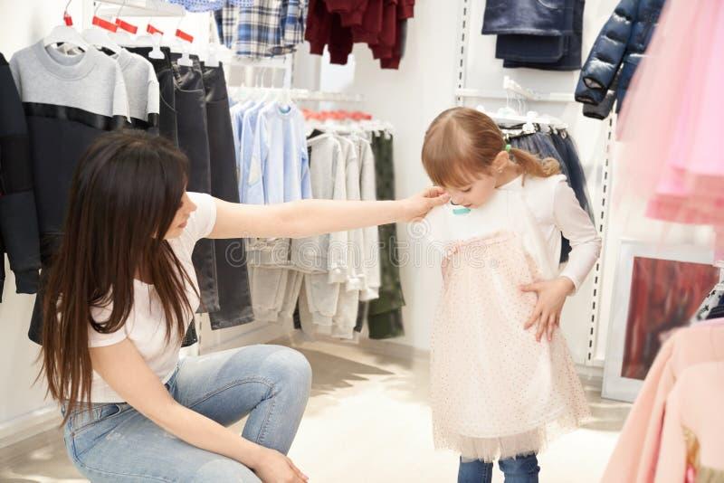 Jonge moeder die roze kleding voor weinig dochter in winkel kiezen stock fotografie