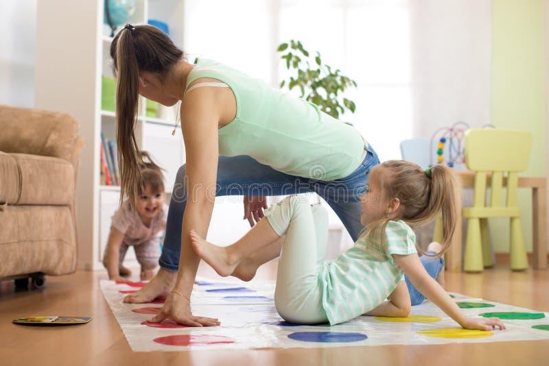 Jonge moeder die twister met haar dochters spelen De gelukkige familie heeft een prettijd in vakantie stock foto