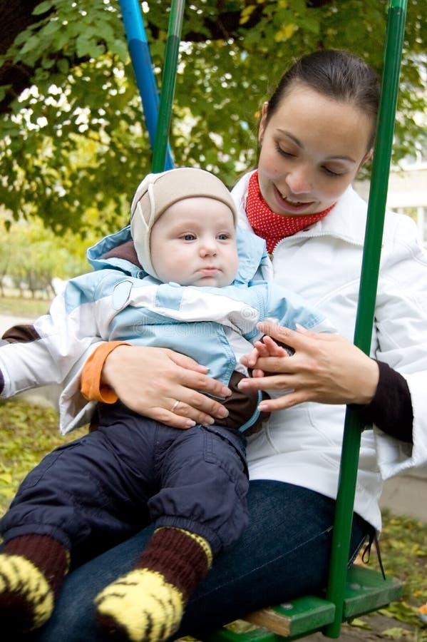 Jonge moeder en babyjongen op schommeling royalty-vrije stock foto's