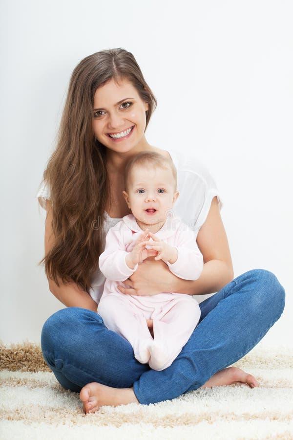 Jonge moeder en babyzitting op tapijt royalty-vrije stock foto's