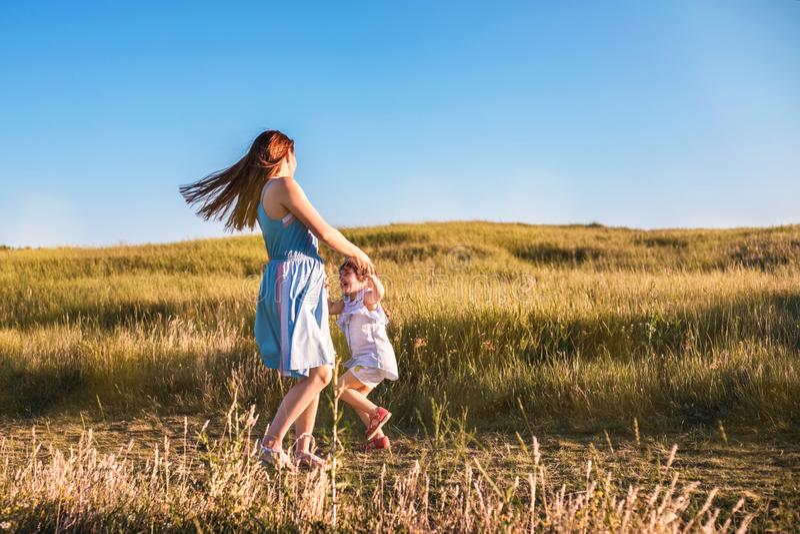 Jonge moeder en dochter die en op een gouden gebied van zonneschijn dansen spelen royalty-vrije stock afbeeldingen