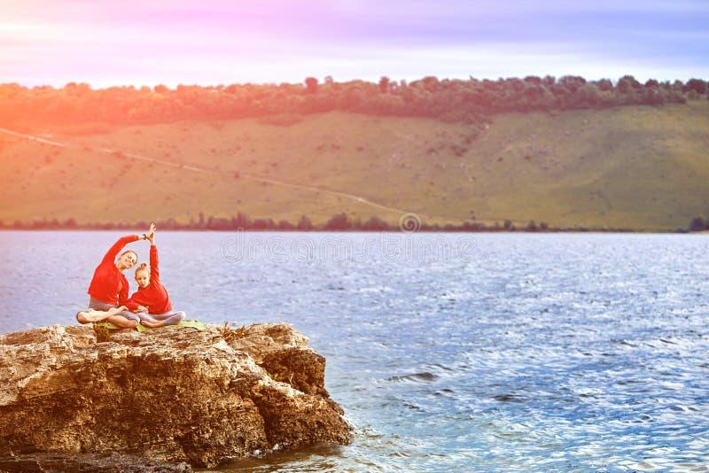 Jonge moeder en dochter die yogaoefeningen op de rots doen dichtbij rivier stock afbeeldingen