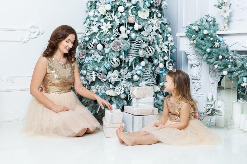 Jonge moeder en dochter onder de Kerstboom stock afbeelding