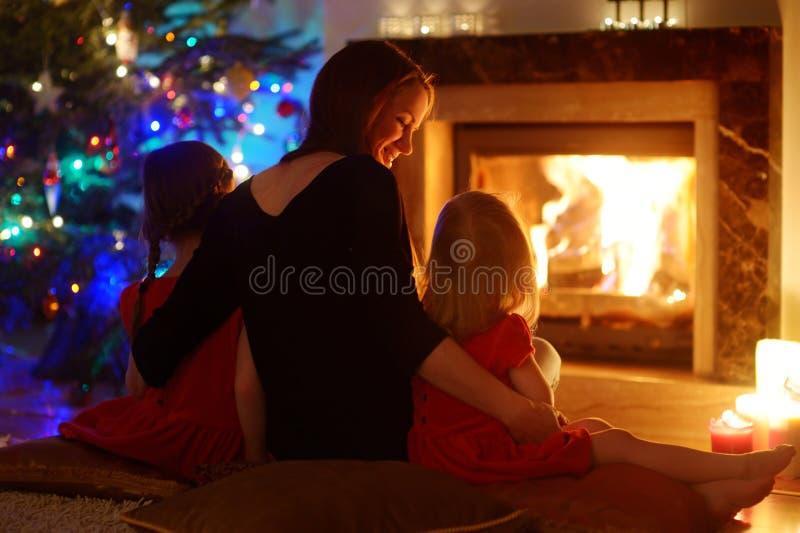 Jonge moeder en dochters die door een open haard op Kerstmis zitten royalty-vrije stock foto's